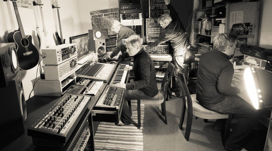 Multiple Copies of Jörg Schaaf sitting together in a black and white room full of synths.